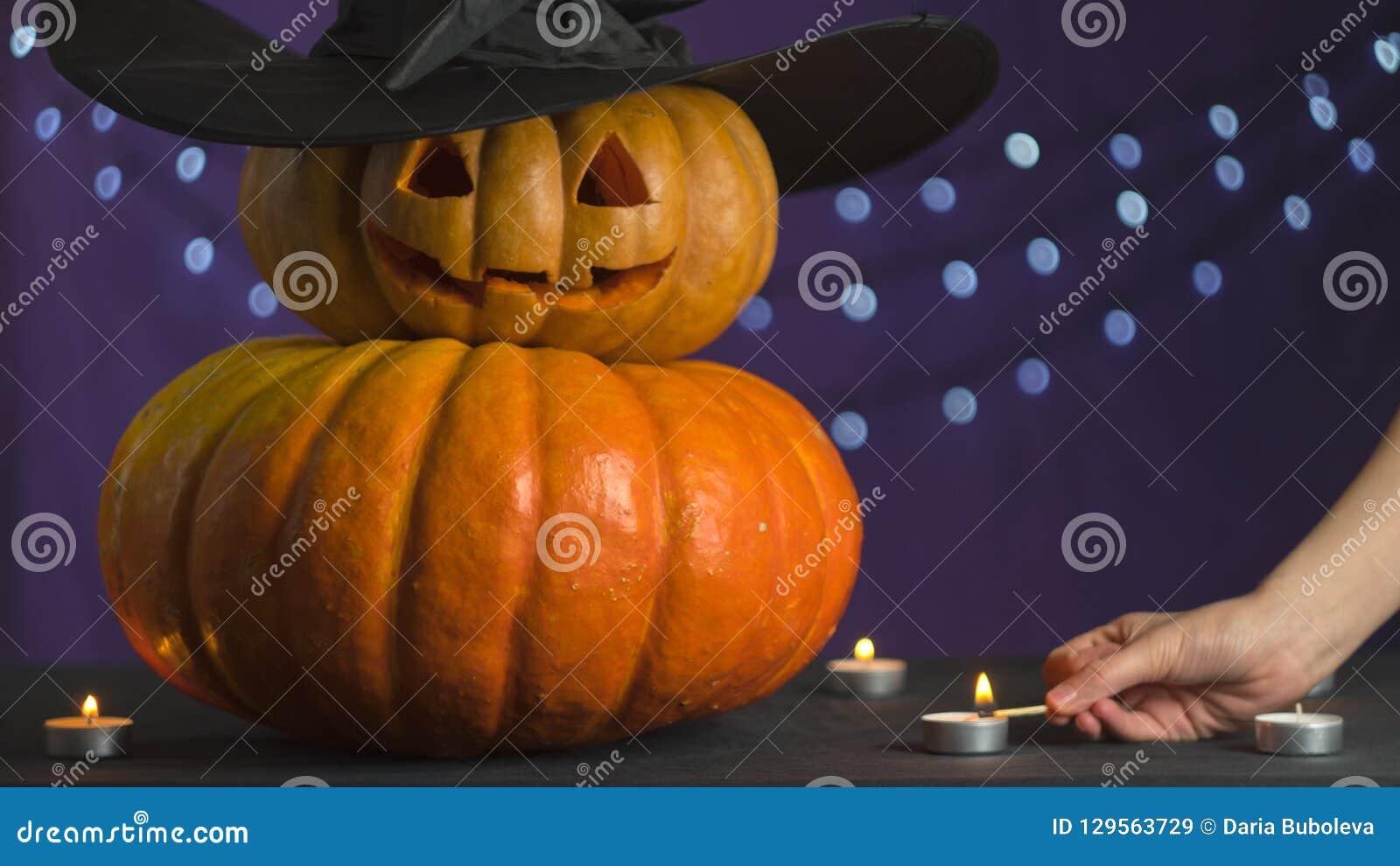 Żeński ręki światło świeczka obok bani dla Halloween