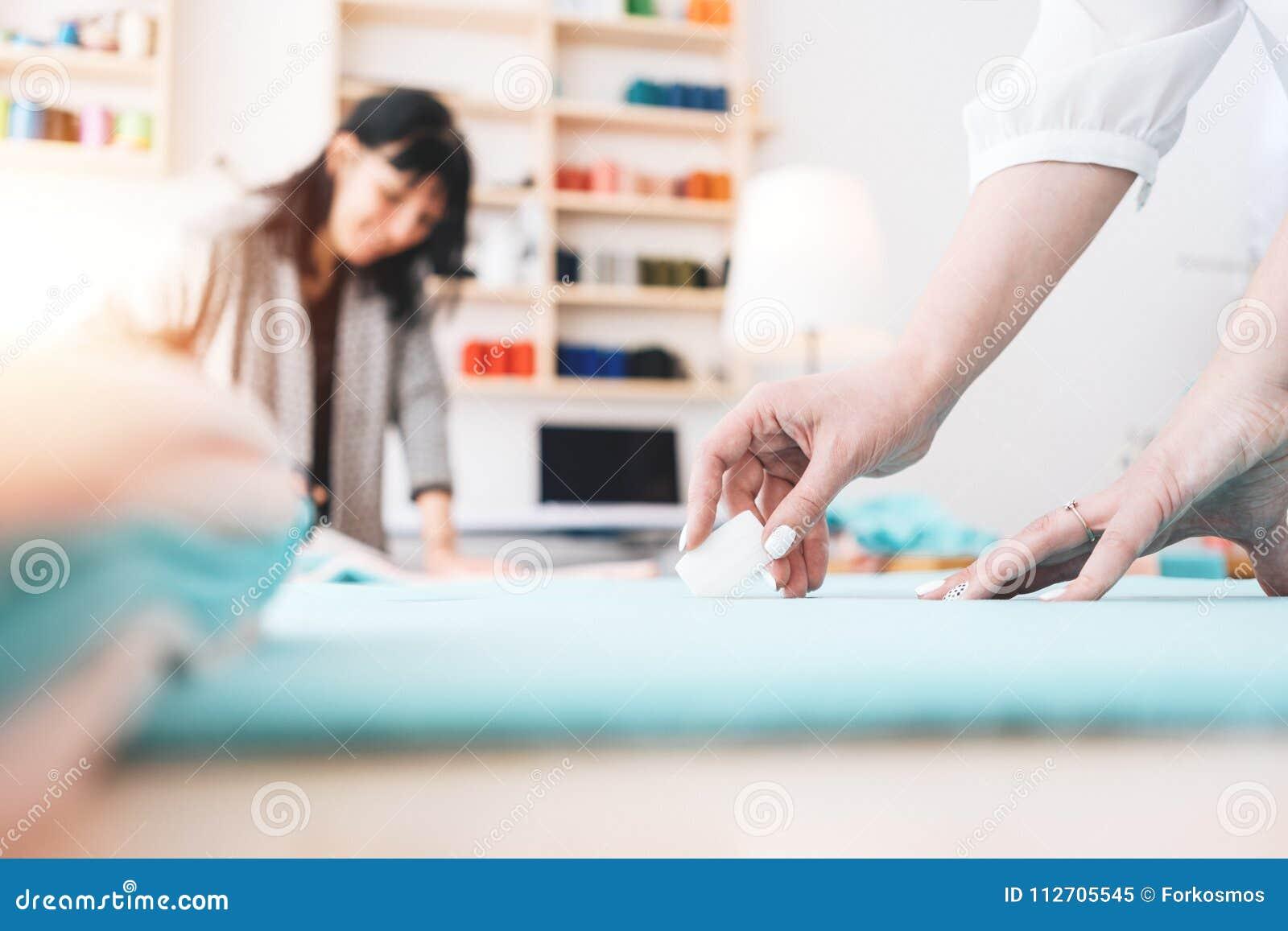 Żeński ręki krawcowej zakończenie Dwa potomstw szwaczka pracuje w loft szwalnym studiu