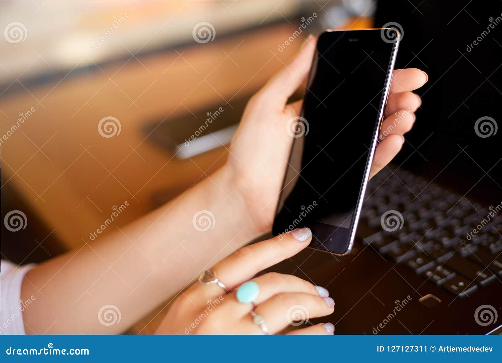 Żeński skanerowanie odcisk palca na jej smartphone z laptopem na backround Kobieta otwiera telefon komórkowego z biometrycznym cz