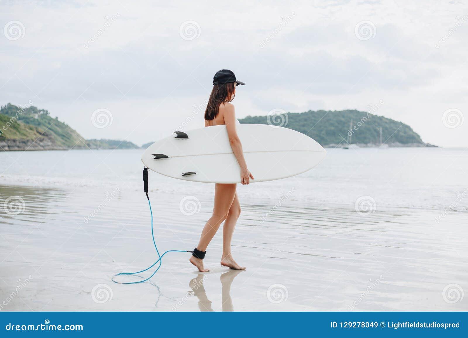 żeński surfingowiec w bikini mienia iść i surfboard
