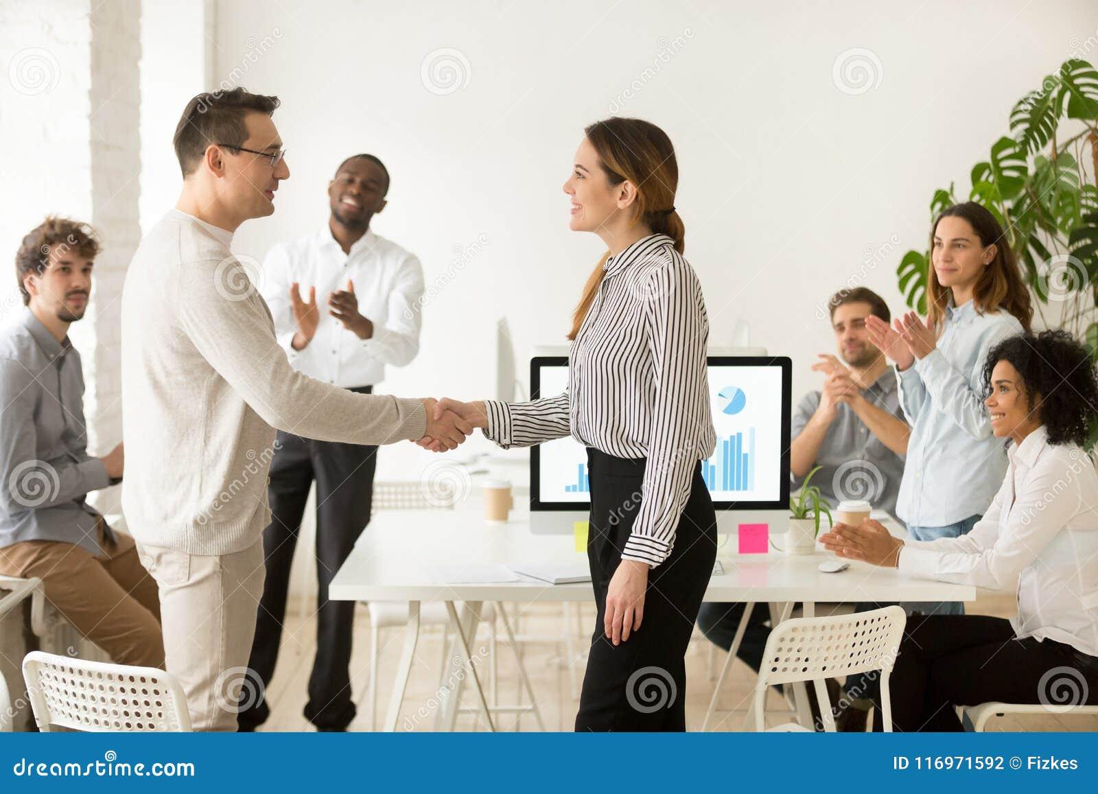 Żeński szef promuje dający satysfakcję handshaking męskiego pracownika podczas gdy