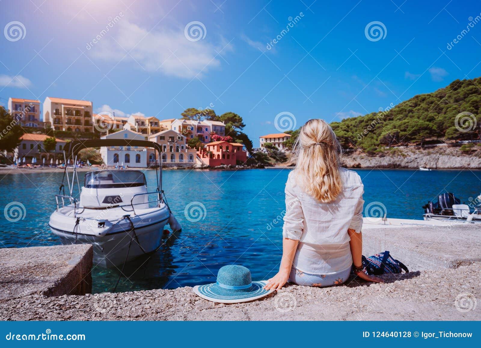 Żeński turystyczny obsiadanie na molu z blau słońca kapeluszem kłaść behind Assos wioska z pięknymi tradycyjnymi domami jest