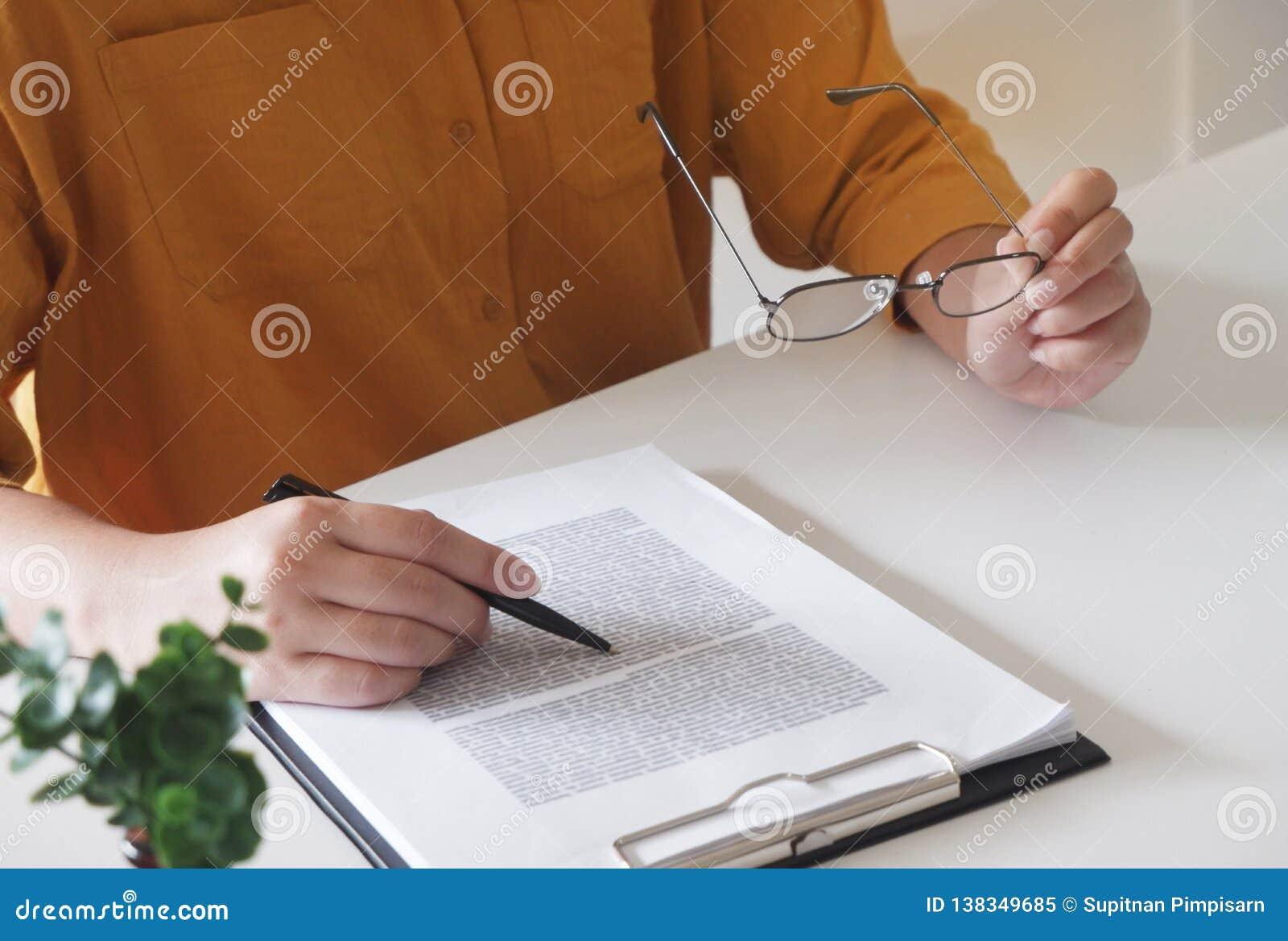 żeński zamknięte żeńskie ręki pisać coś i trzymać szkła w jej biurze