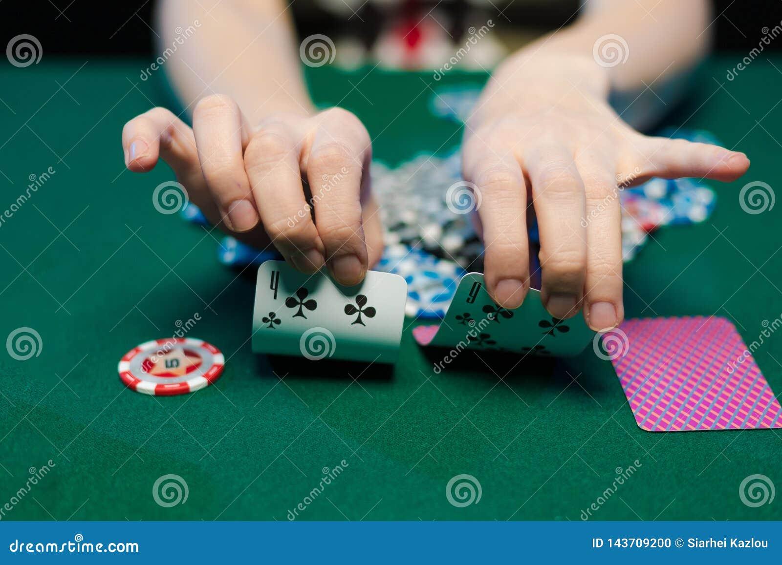 Żeńskie ręki rozkładają karty do gry i układy scalonych w kasynie
