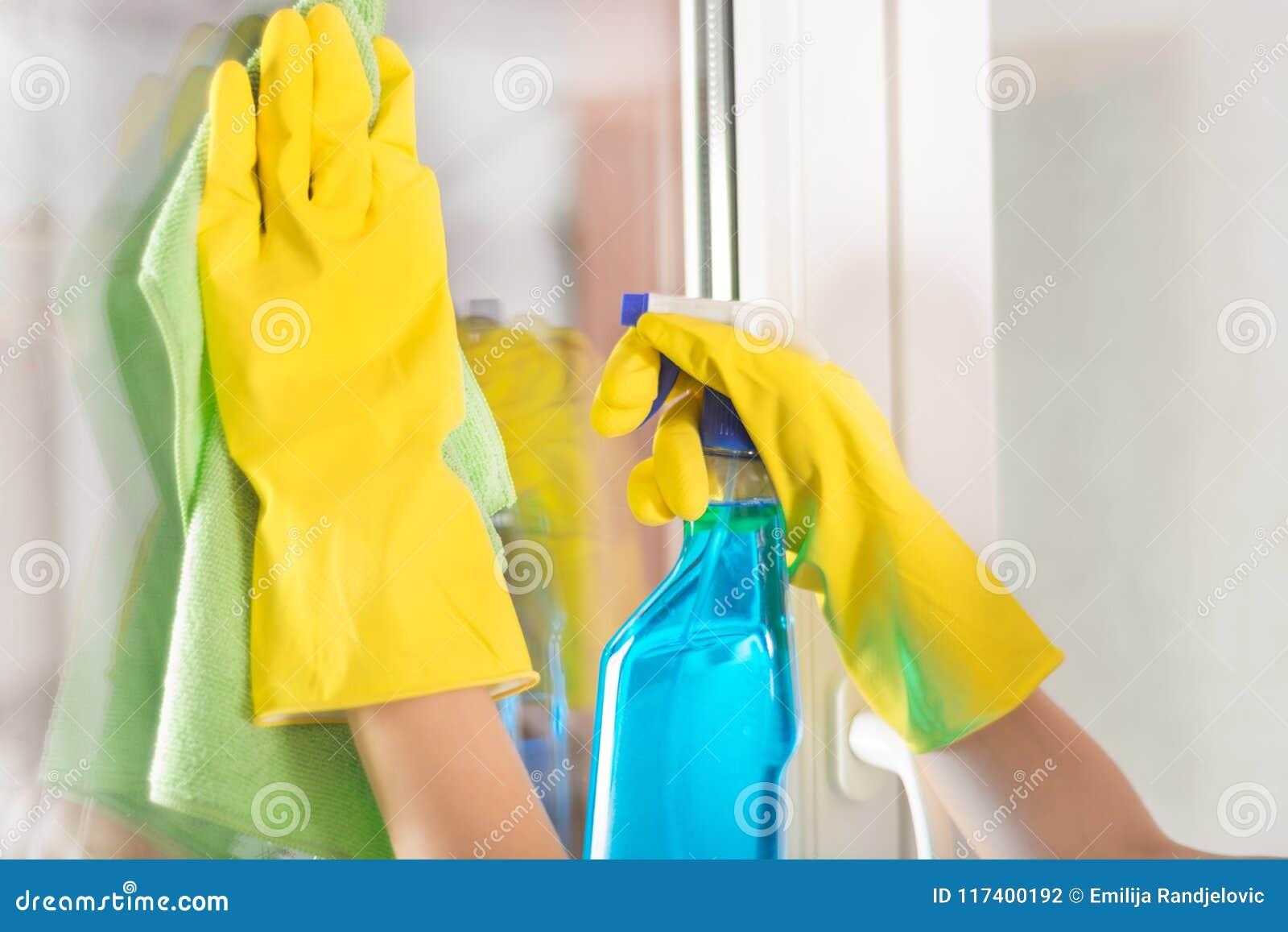 Żeńskie ręki z żółtymi ochronnymi rękawiczkami czyści okno używa zieleń łachman i detergentową kiść w domu
