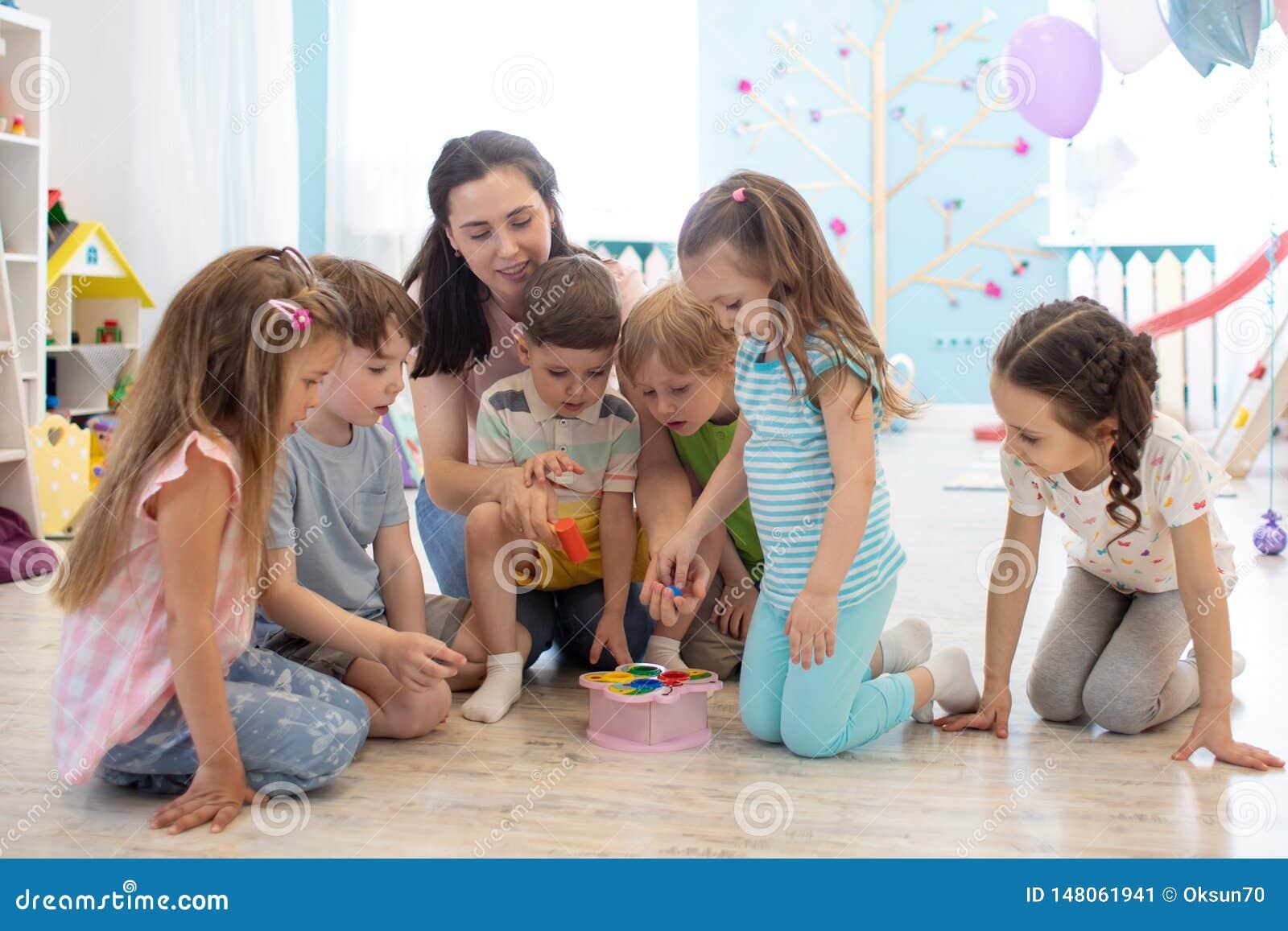 Żeńskiego nauczyciela nauczanie żartuje sztuki zabawkę w klasowym pokoju Dziecina preschool pojęcie