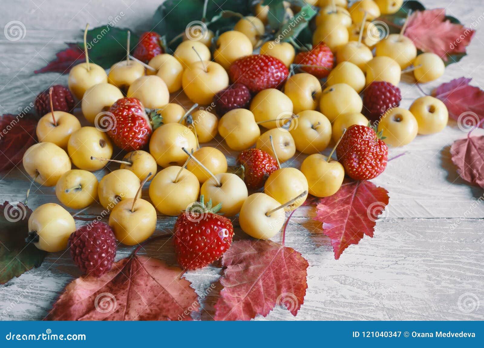 Żniwo jesieni jabłka i piękny czerwony liść na drewnianym tle