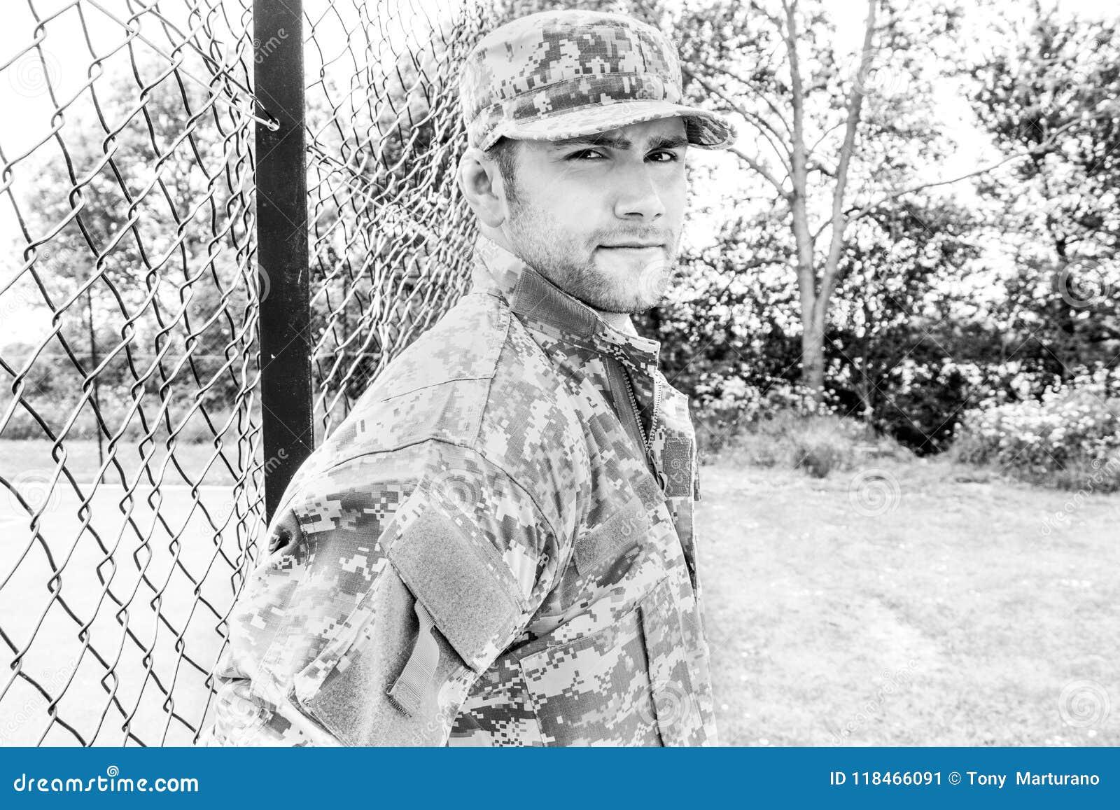 Żołnierz piechoty morskiej, żołnierz w jego wojsku męczy stojaki uwaga przy militarną bazą