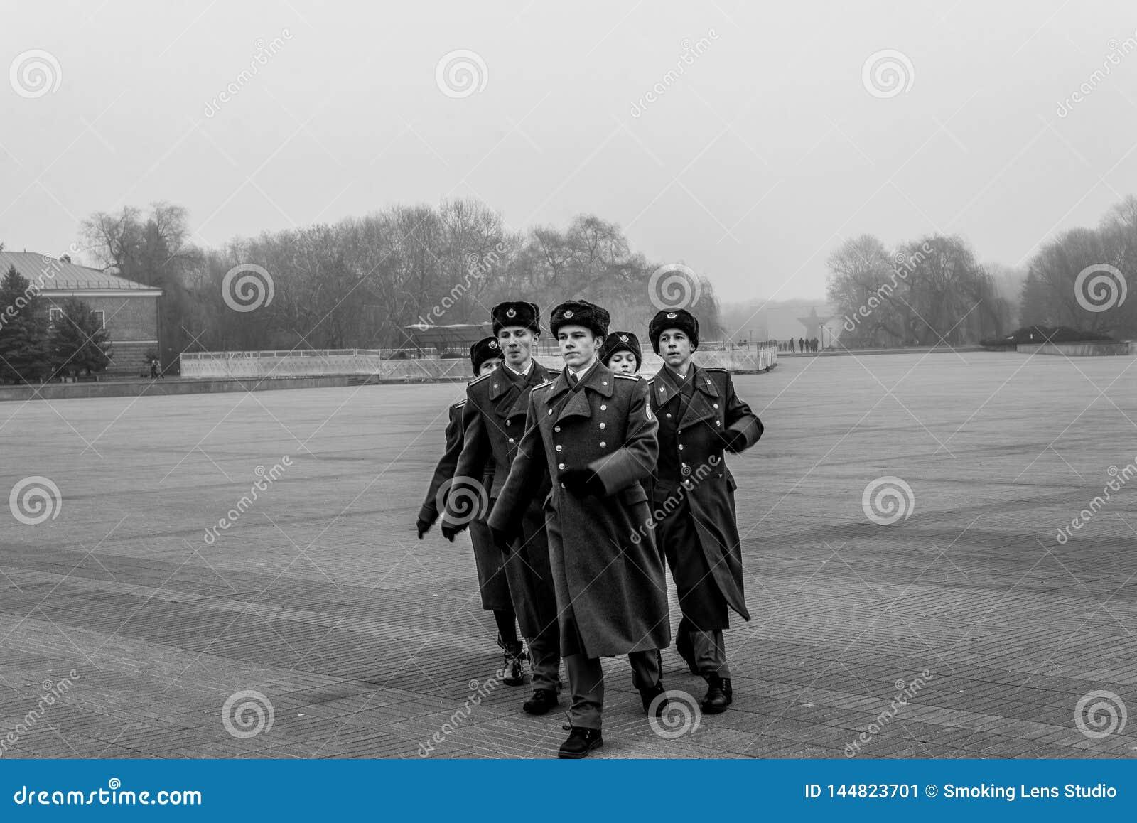 Żołnierze maszeruje uznanie wojenny pomnik i płaci
