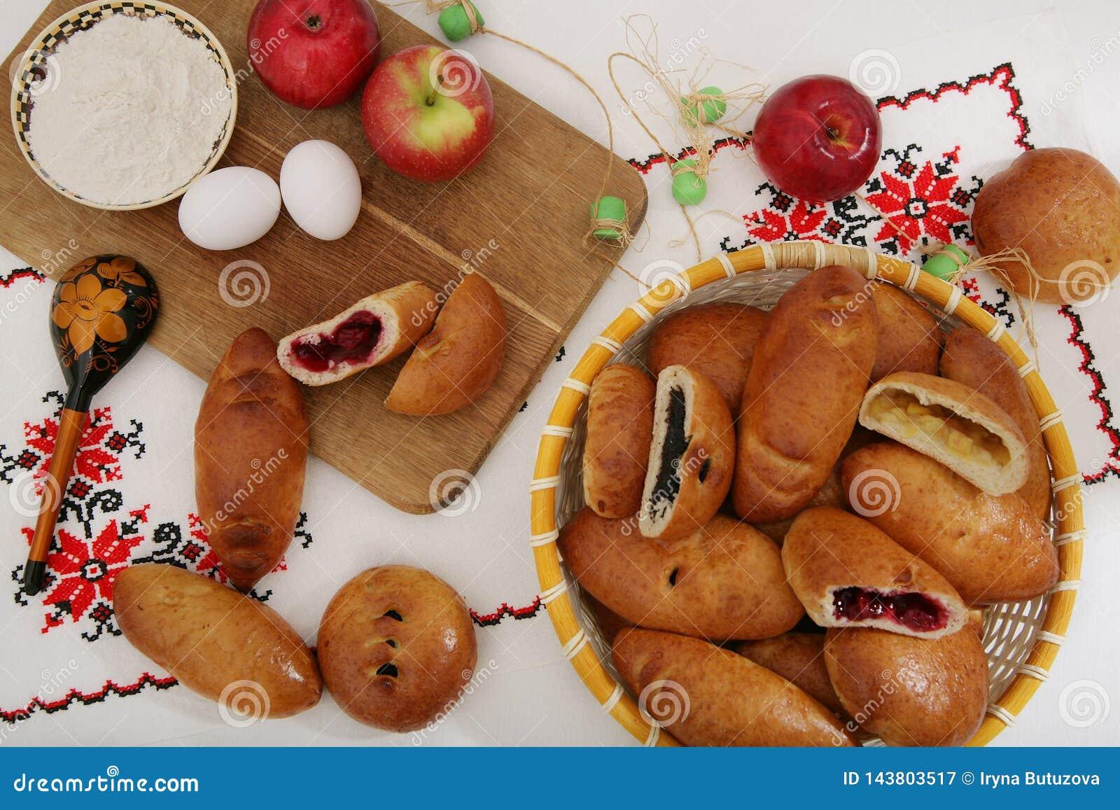 Życie z tradycyjnymi Rosyjskimi kulebiakami, składniki - mąka, jajka, jabłka Na autentycznym tablecloth z drewnianą łyżką z pa