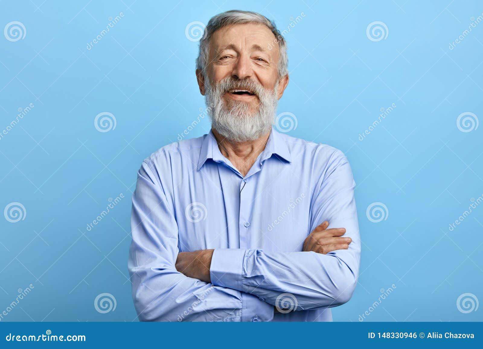 Życzliwa przystojna mężczyzna pozycja z krzyżować rękami, śmia się przy coś