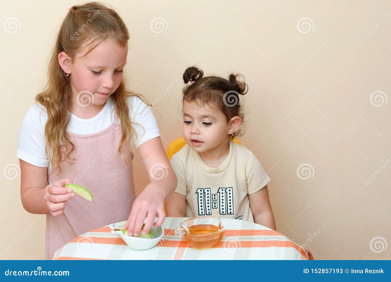 Żydowscy dzieci zamacza jabłko plasterki w miód na Rosh HaShanah