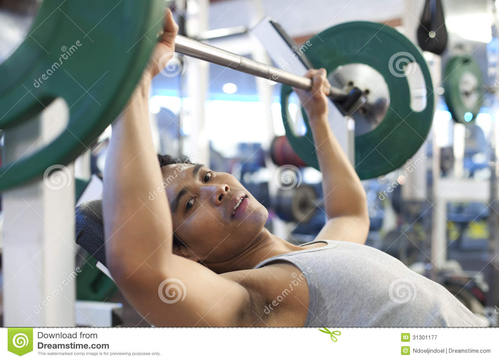 亚洲人健身房锻炼,使用在看照相机的健身俱乐部的一
