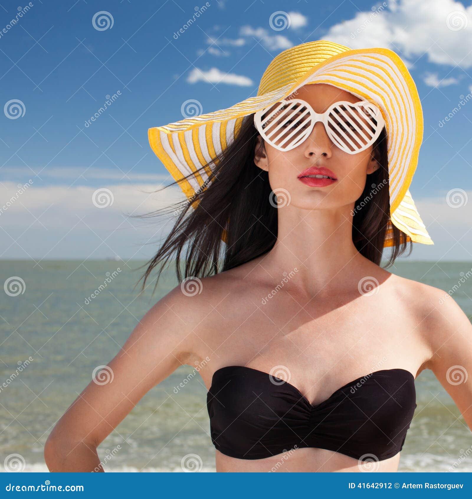 时髦的泳装的妇女在海滩