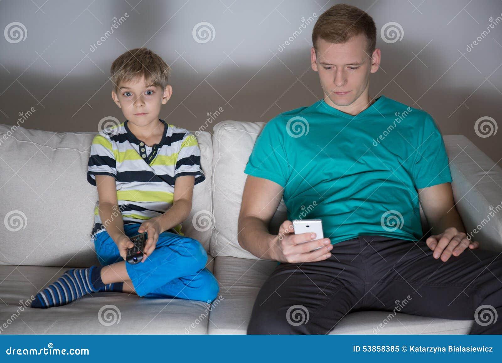使用电话的孩子看电视的和爸爸 库存照片 - 图片