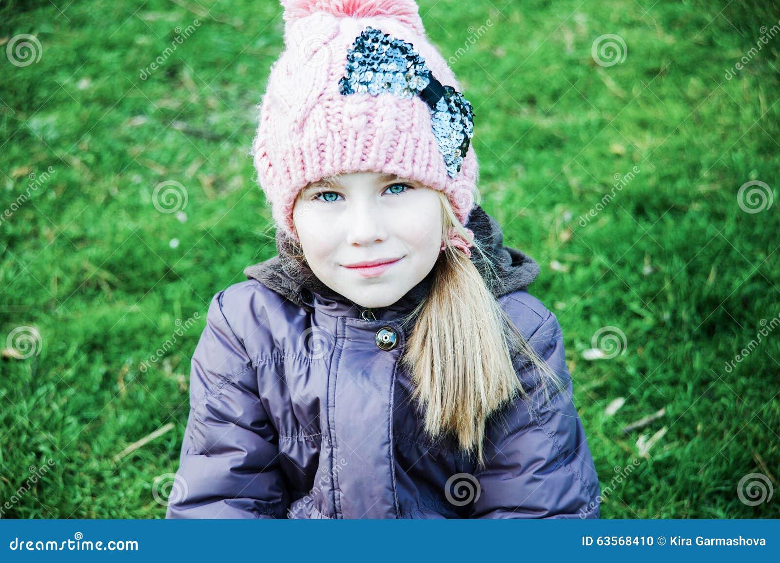 在秋天美丽的小女孩的室外画象有长的头发的坐在桃红色帽子的一棵草.图片