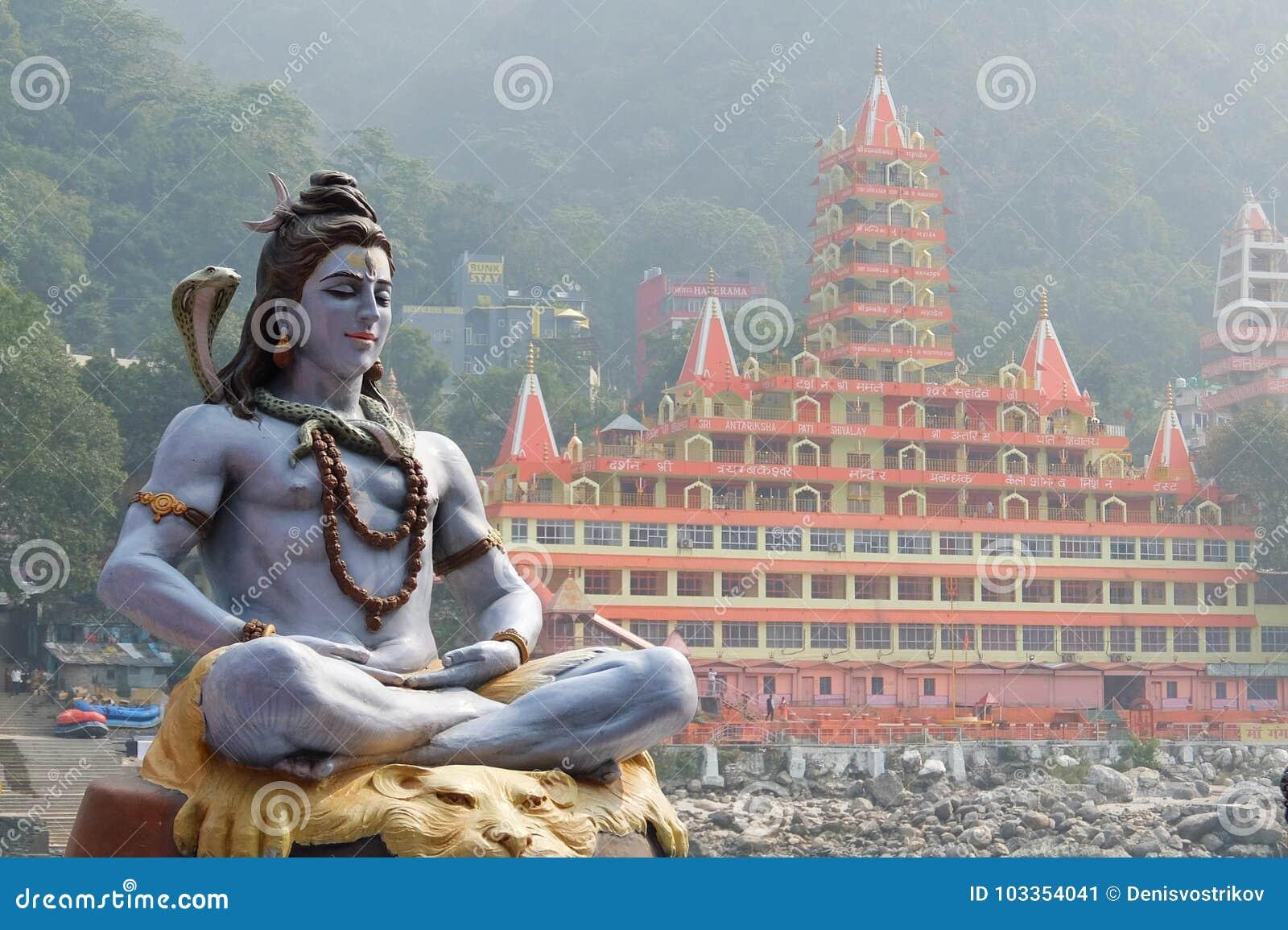 Άγαλμα της συνεδρίασης Shiva στην περισυλλογή στο riverbank Ganga σε Rishikesh, ναός Tera Manzil, Trayambakeshwar στο υπόβαθρο