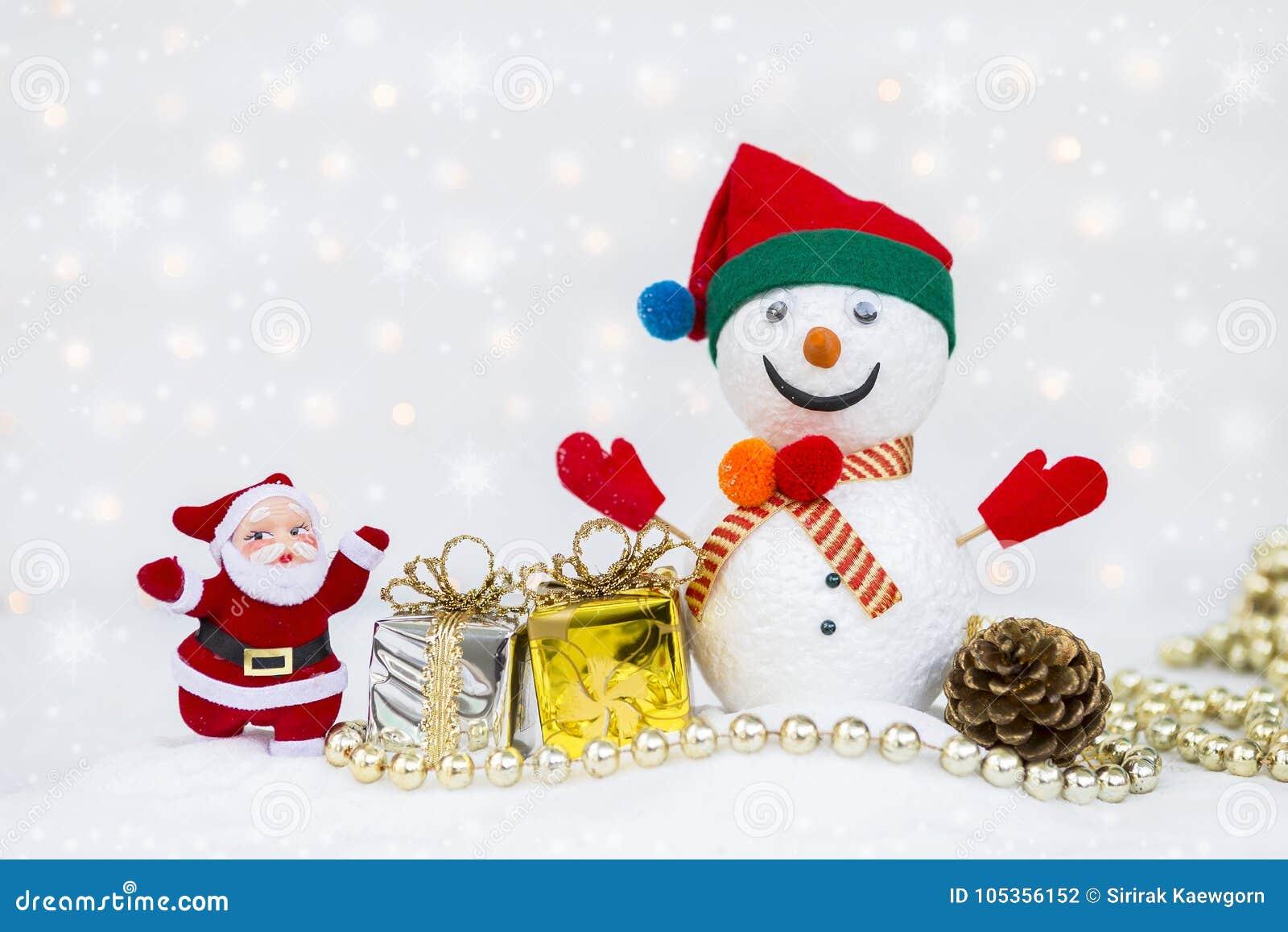 Άγιος Βασίλης και άτομο χιονιού με το ασημένιο και χρυσό κιβώτιο δώρων πέρα από θολωμένος bokeh