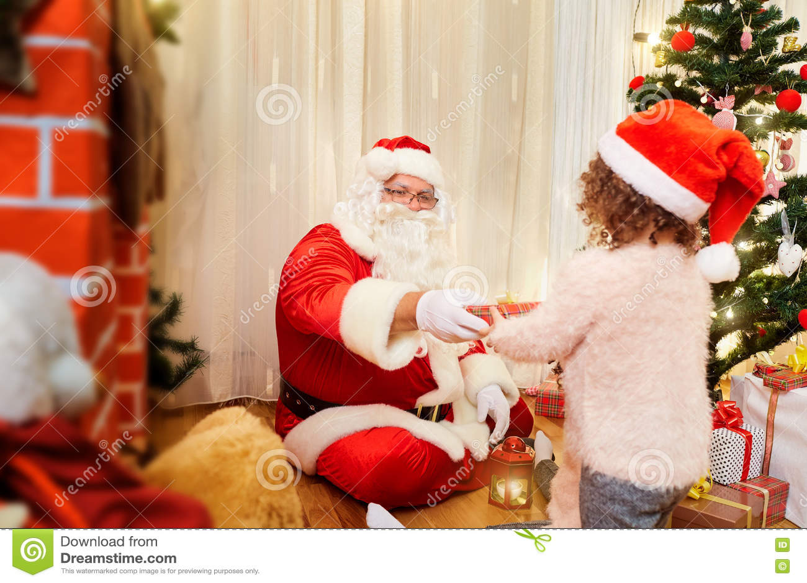 Άγιος Βασίλης δίνει στο παιδί ένα δώρο για τα Χριστούγεννα στο εσωτερικό σε ένα ro