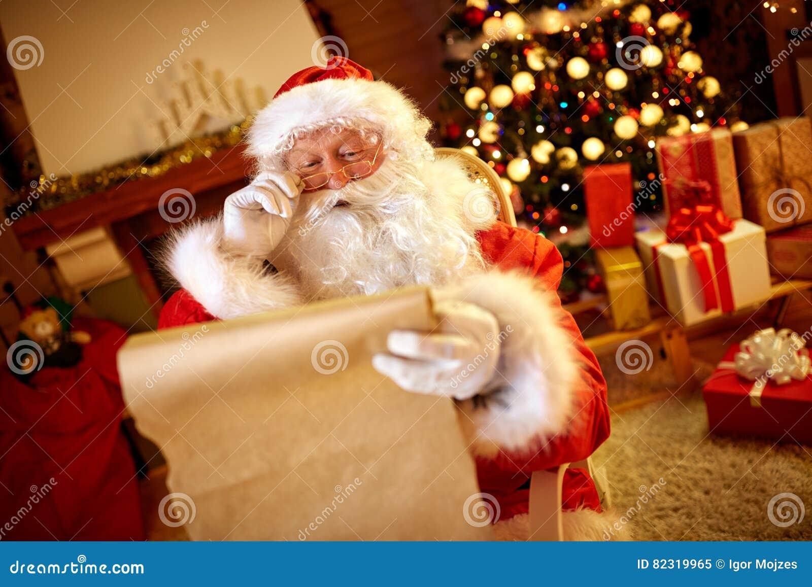 Άγιος Βασίλης που εξετάζει το μακρύ κατάλογο με την επιθυμία παιδιών