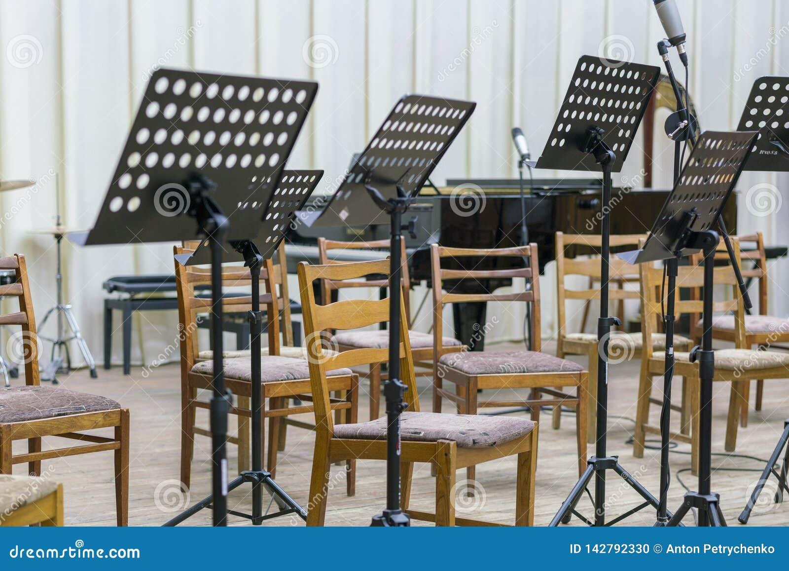 Άδειες θέσεις και μερικά όργανα στο μέγαρο μουσικής που αναμένει την ορχήστρα για να έρθει στο στάδιο μαύρη στάση μουσικής στη σκ