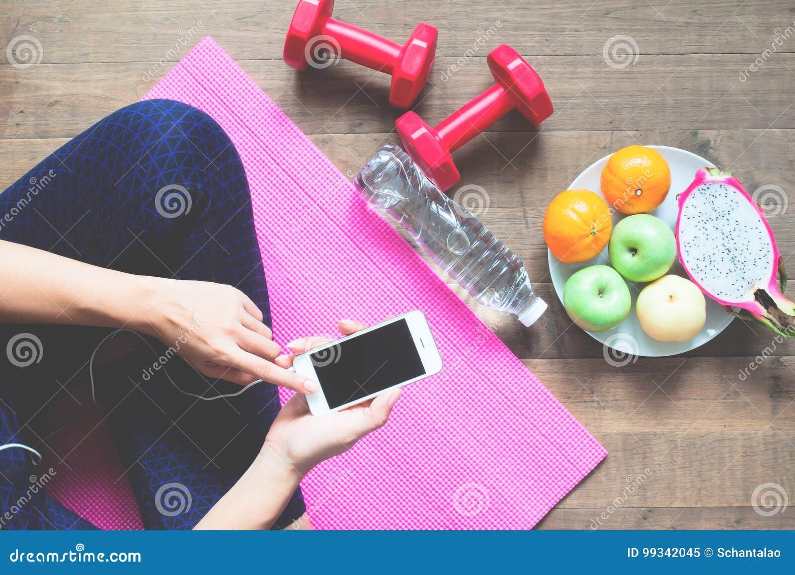 Άμεσα ανωτέρω της γυναίκας στον ιματισμό ικανότητας που χρησιμοποιεί το κινητό τηλέφωνο με τους αθλητικούς εξοπλισμούς και τα φρο