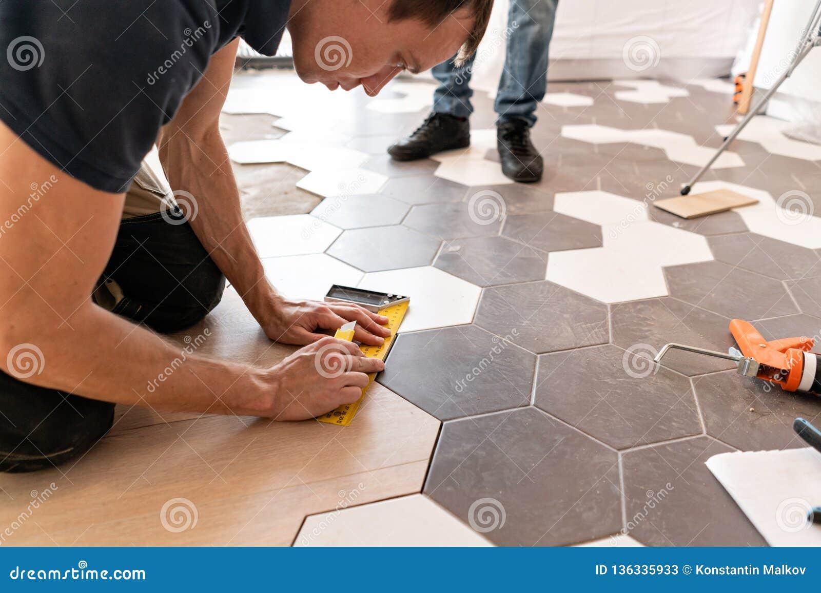 Άνδρας εργαζόμενος που εγκαθιστά το νέο ξύλινο φυλλόμορφο δάπεδο Ο συνδυασμός ξύλινων επιτροπών των φυλλόμορφων και κεραμικών κερ