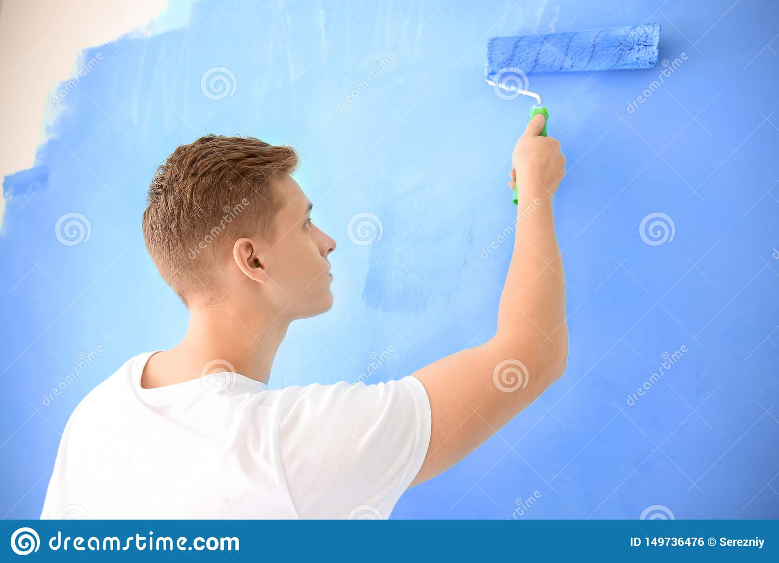 Άνδρας ζωγράφος που χρησιμοποιεί τον κύλινδρο για να ανανεώσει το χρώμα του τοίχου στο εσωτερικό