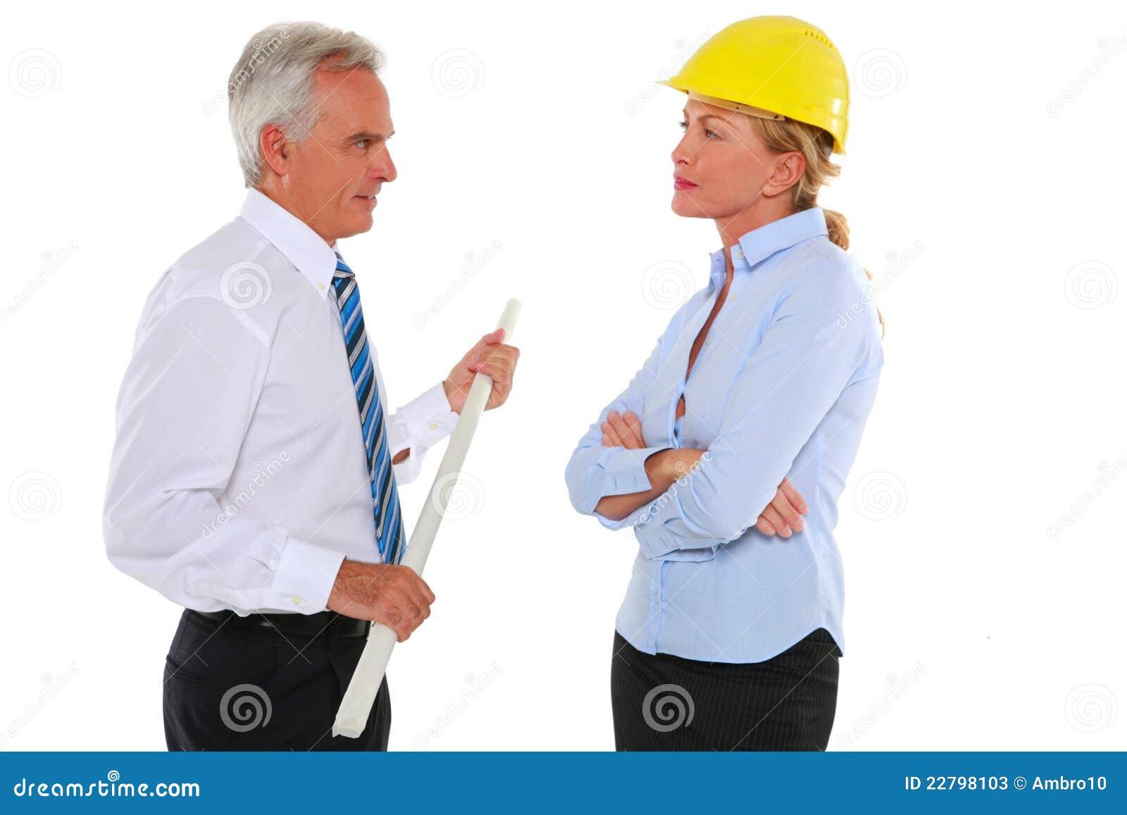 Άνδρας με τον αρχιτέκτονα σχεδίων και γυναικών με το σκληρό καπέλο