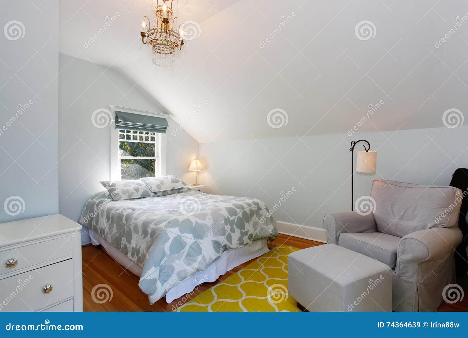 Άνετη αττική κρεβατοκάμαρα με τους άσπρους τοίχους και την κίτρινη κουβέρτα 83c837ce7fa
