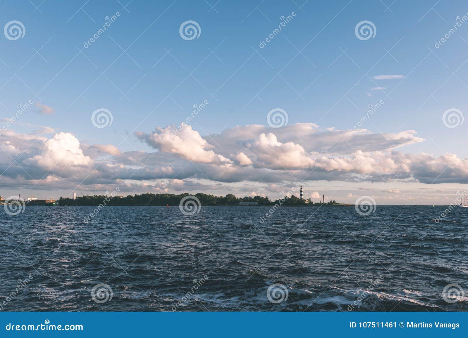 Άνετη παραλία της θάλασσας της Βαλτικής με τους βράχους και το πράσινο vegetat