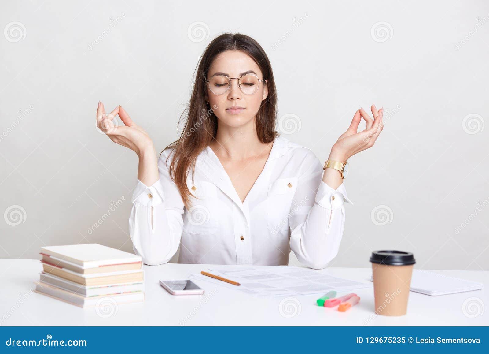 Άνθρωποι και έννοια πνευματικότητας Το χαλαρωμένο brunette που η νέα γυναίκα θέτει στον εργασιακό χώρο στο σημάδι mudra, απολαμβά