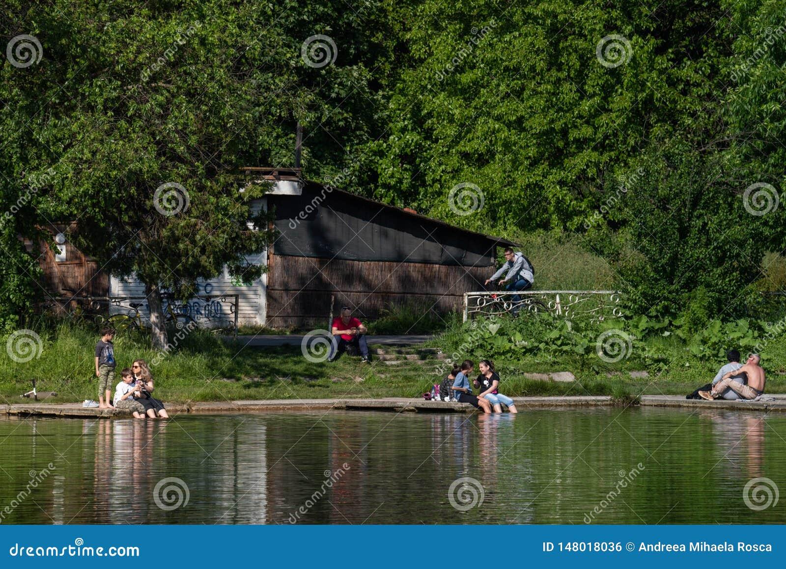 Άνθρωποι που έχουν έναν χρόνο διασκέδασης σε μια θερμή ημέρα κοντά στη λίμνη