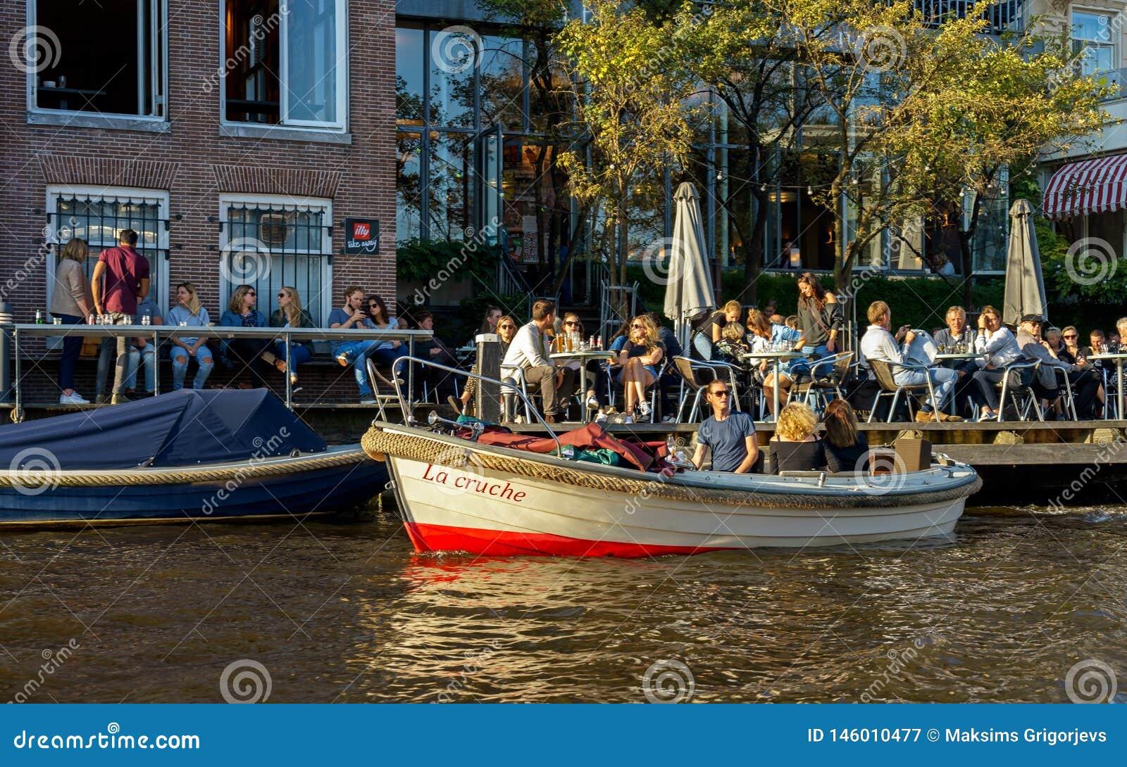 Άνθρωποι που κάθονται στο εστιατόριο καφέδων στο κανάλι στο Άμστερνταμ με τη σταθμευμένη μικρή βάρκα γύρου πόλεων, οι Κάτω Χώρες,
