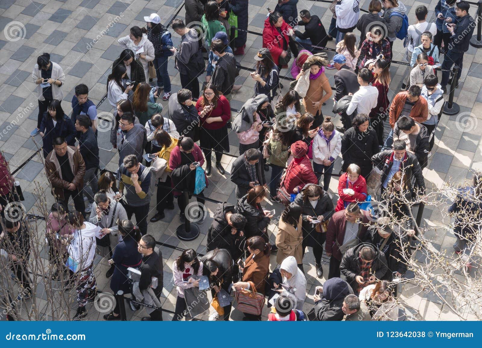 Άνθρωποι που περιμένουν στη σειρά επάνω για ένα γεγονός σε μια λεωφόρο αγορών στο Πεκίνο