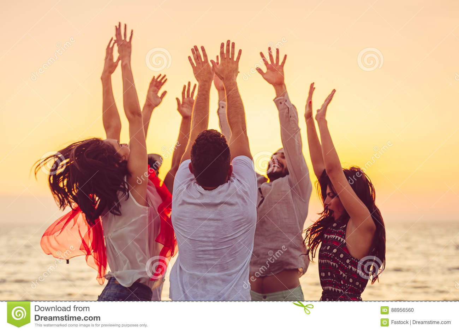 Άνθρωποι που χορεύουν στην παραλία με τα χέρια επάνω έννοια για το κόμμα, τη μουσική και τους ανθρώπους