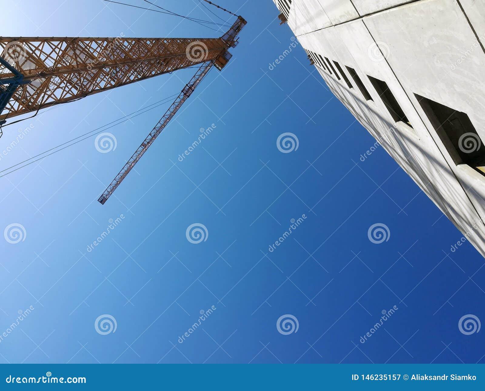 Άνοδοι γερανών οικοδόμησης επάνω από το κτήριο Κατώτατο σημείο επάνω στην άποψη σχετικά με το υπόβαθρο μπλε ουρανού