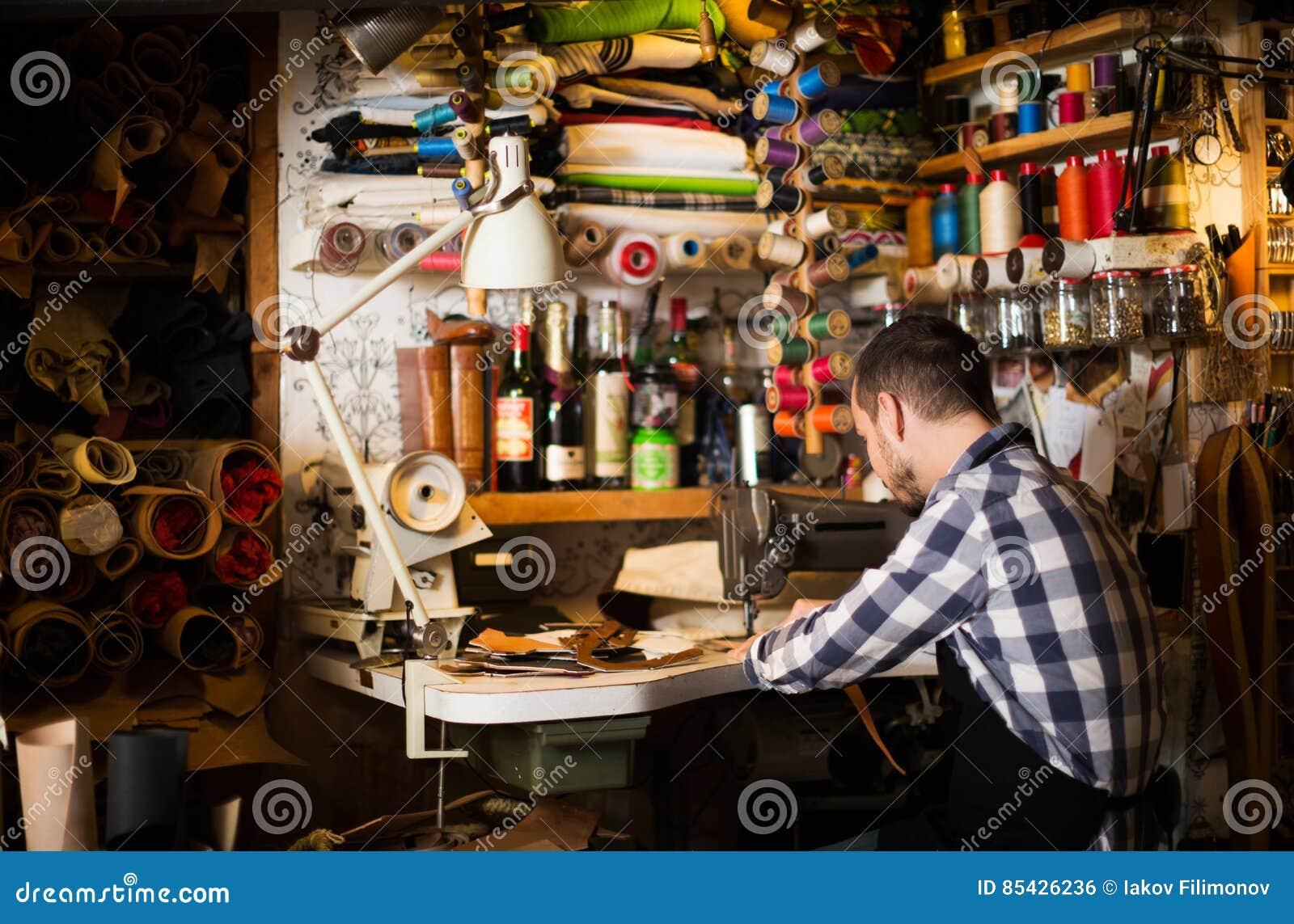 Άνδρας εργαζόμενος που ράβει τη νέα ζώνη