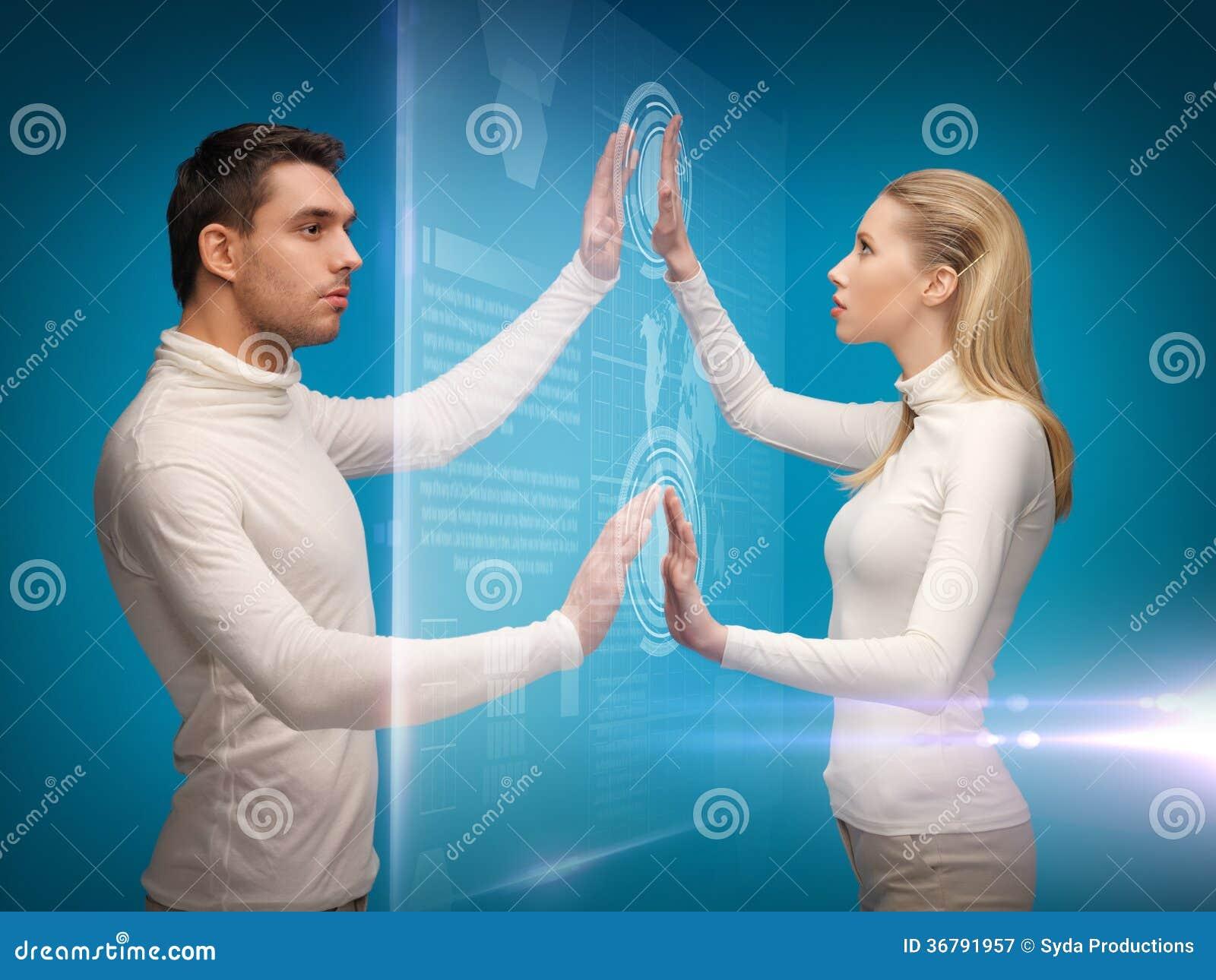 Άνδρας και γυναίκα που εργάζονται με τις εικονικές οθόνες