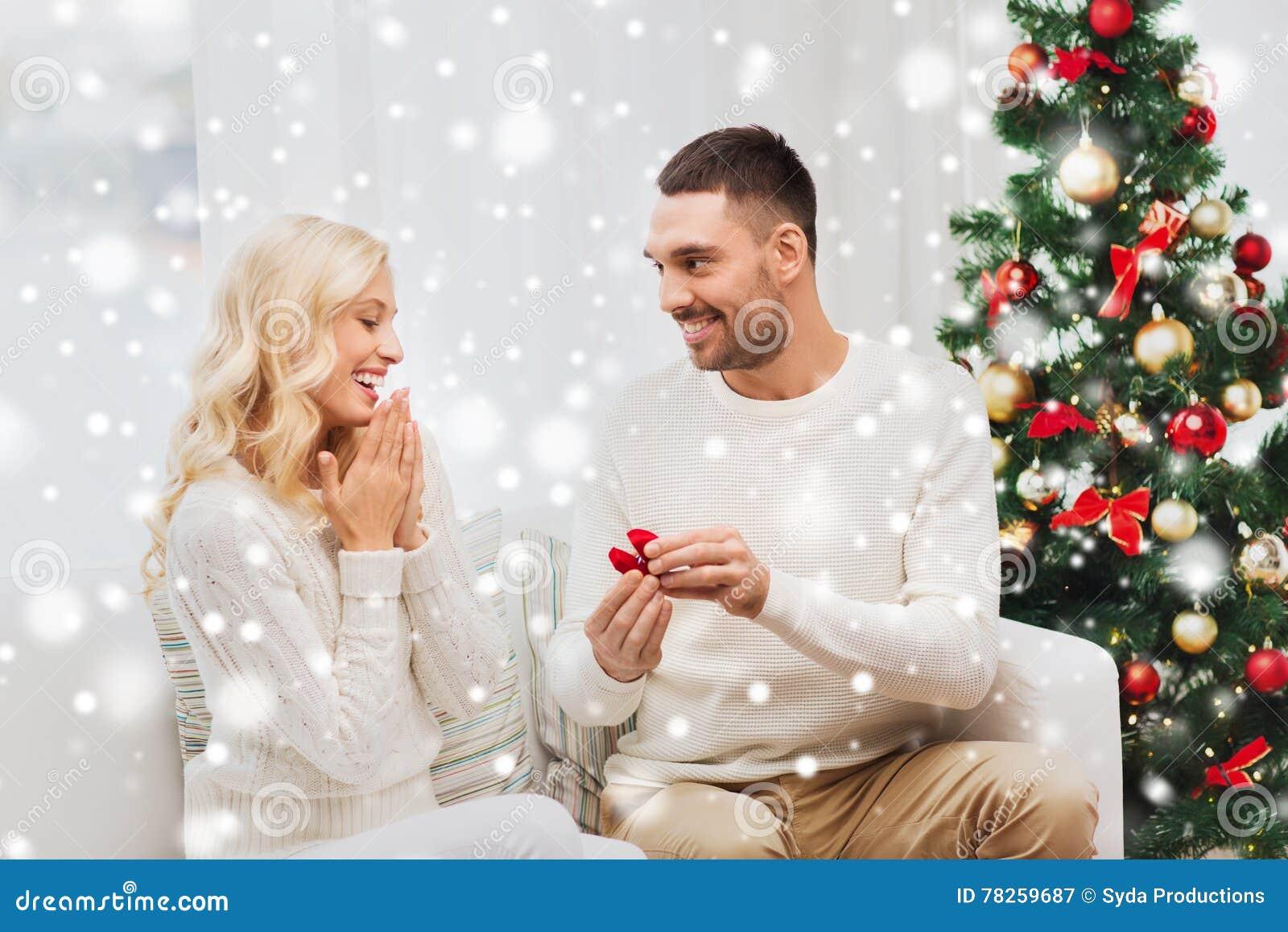 Άνδρας που δίνει το δαχτυλίδι αρραβώνων γυναικών για τα Χριστούγεννα