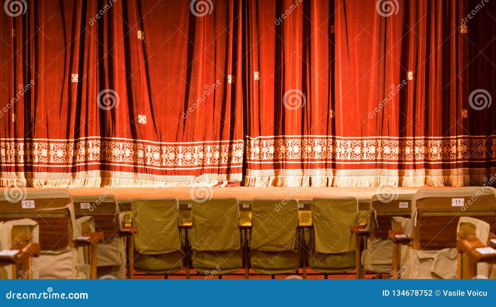 Άποψη από μέσα από ένα θέατρο με τις σκηνικές καρέκλες και την κόκκινη κουρτίνα