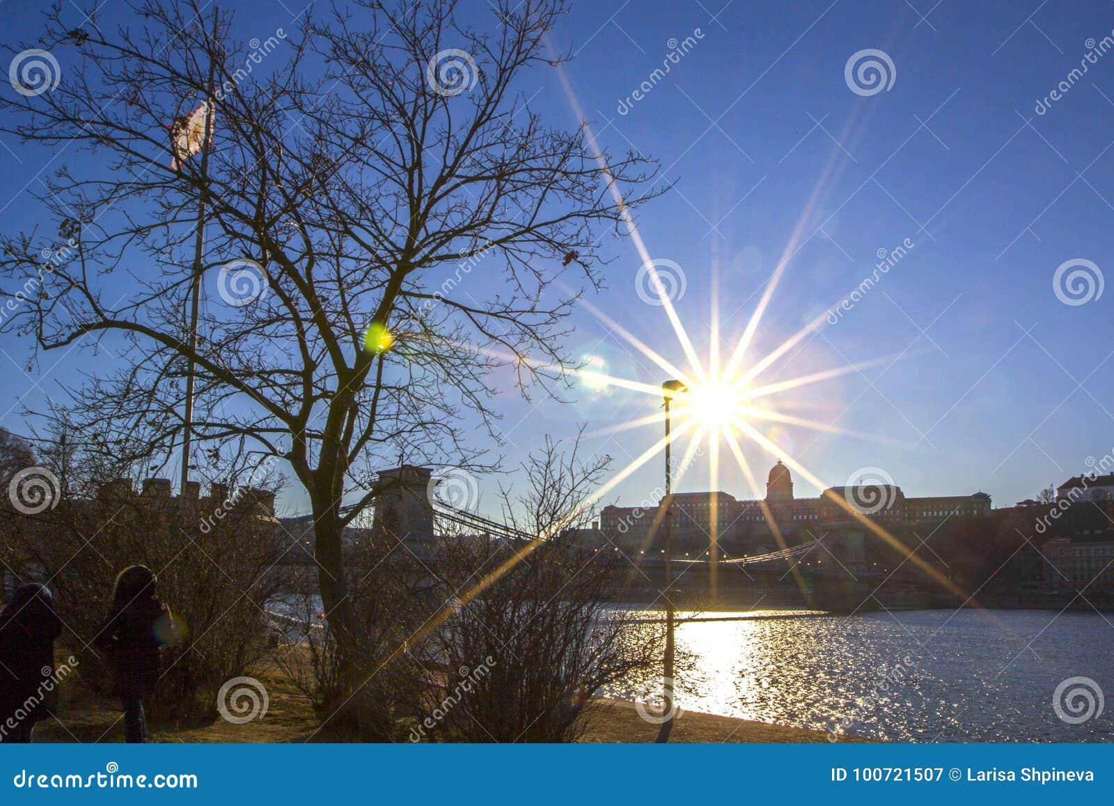 Άποψη ηλιοβασιλέματος πέρα από τον ποταμό Δούναβη, τη βάρκα επιβατών και την πλευρά Buda της Βουδαπέστης, Ουγγαρία