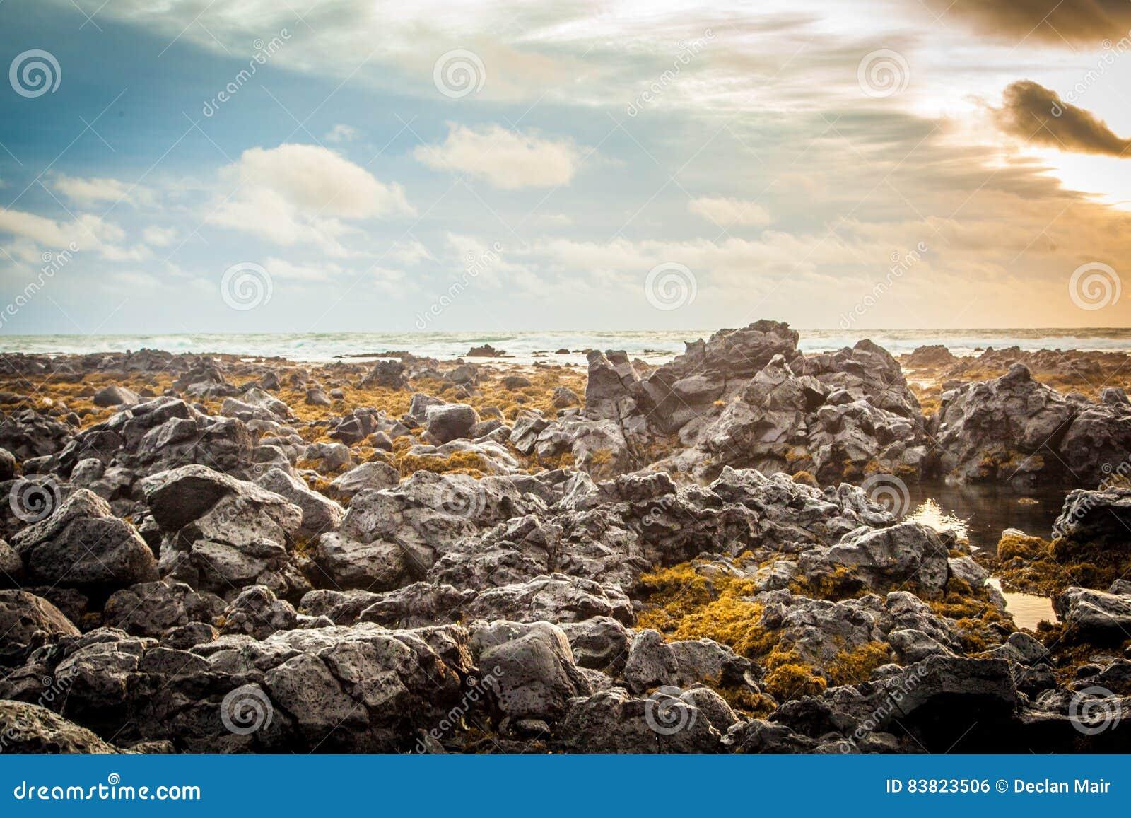 Άποψη θάλασσας των λόφων, του ουρανού και του βράχου