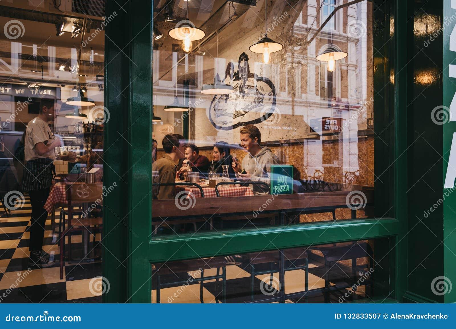 Άποψη μέσω του παραθύρου των ανθρώπων μέσα σε ένα εστιατόριο στον κήπο Covent, Λονδίνο, UK
