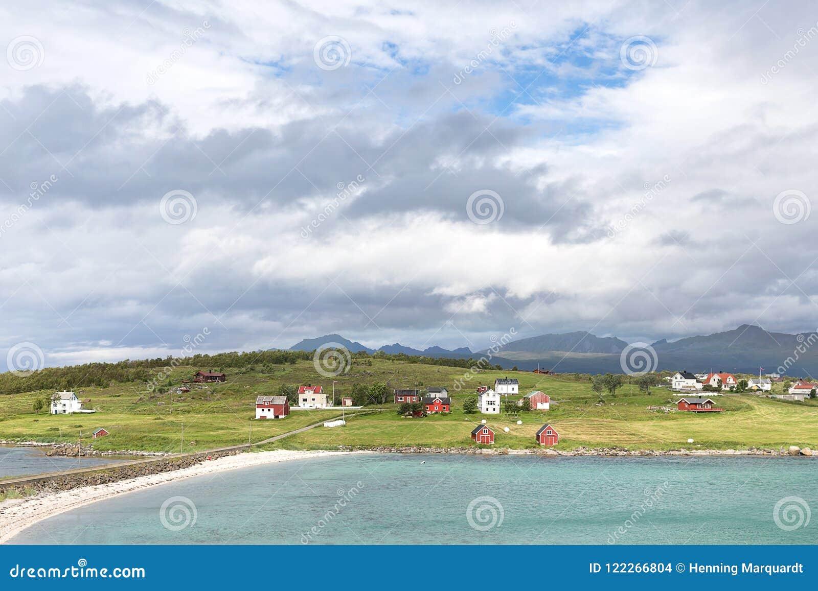 Άποψη πέρα από ένα νορβηγικό φιορδ σε ένα νησί με την αλιεία των καλυβών και του ρ
