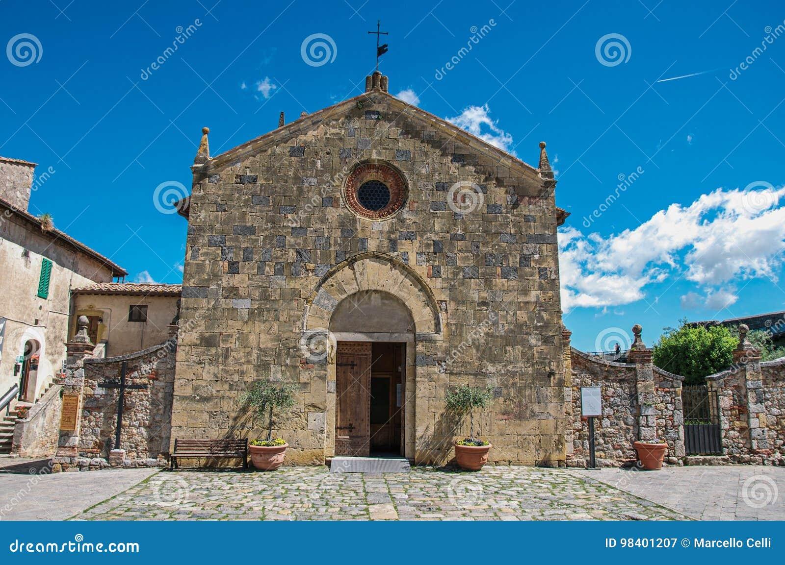Άποψη προσόψεων μιας παλαιάς εκκλησίας σε μια ηλιόλουστη ημέρα στο χωριουδάκι Monteriggioni