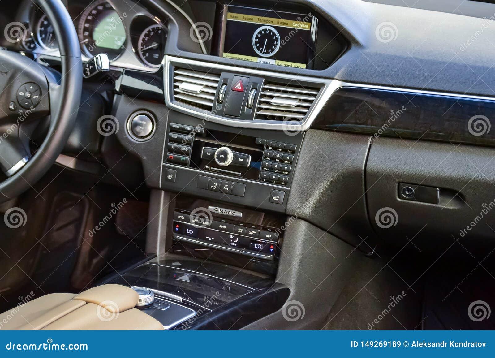 Άποψη στο άσπρο εσωτερικό της ε-κατηγορίας W212 της Mercedes με το ταμπλό, ρολόι, σύστημα μέσων, μπροστινά καθίσματα και shiftgea
