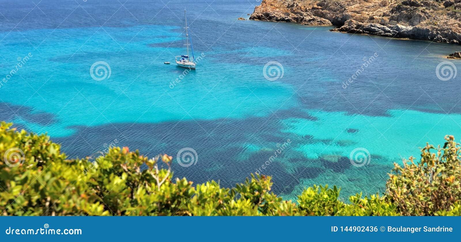 Άποψη σχετικά με μια βάρκα που σταματούν στη σαφή και τυρκουάζ θάλασσα