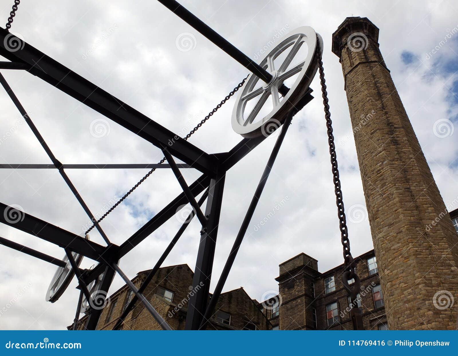 Άποψη της ιστορικής γέφυρας αλυσίδων καναλιών σε Huddersfield Δυτικό Γιορκσάιρ με το μεγάλο παλαιό κτήριο μύλων με μια ψηλή καπνο