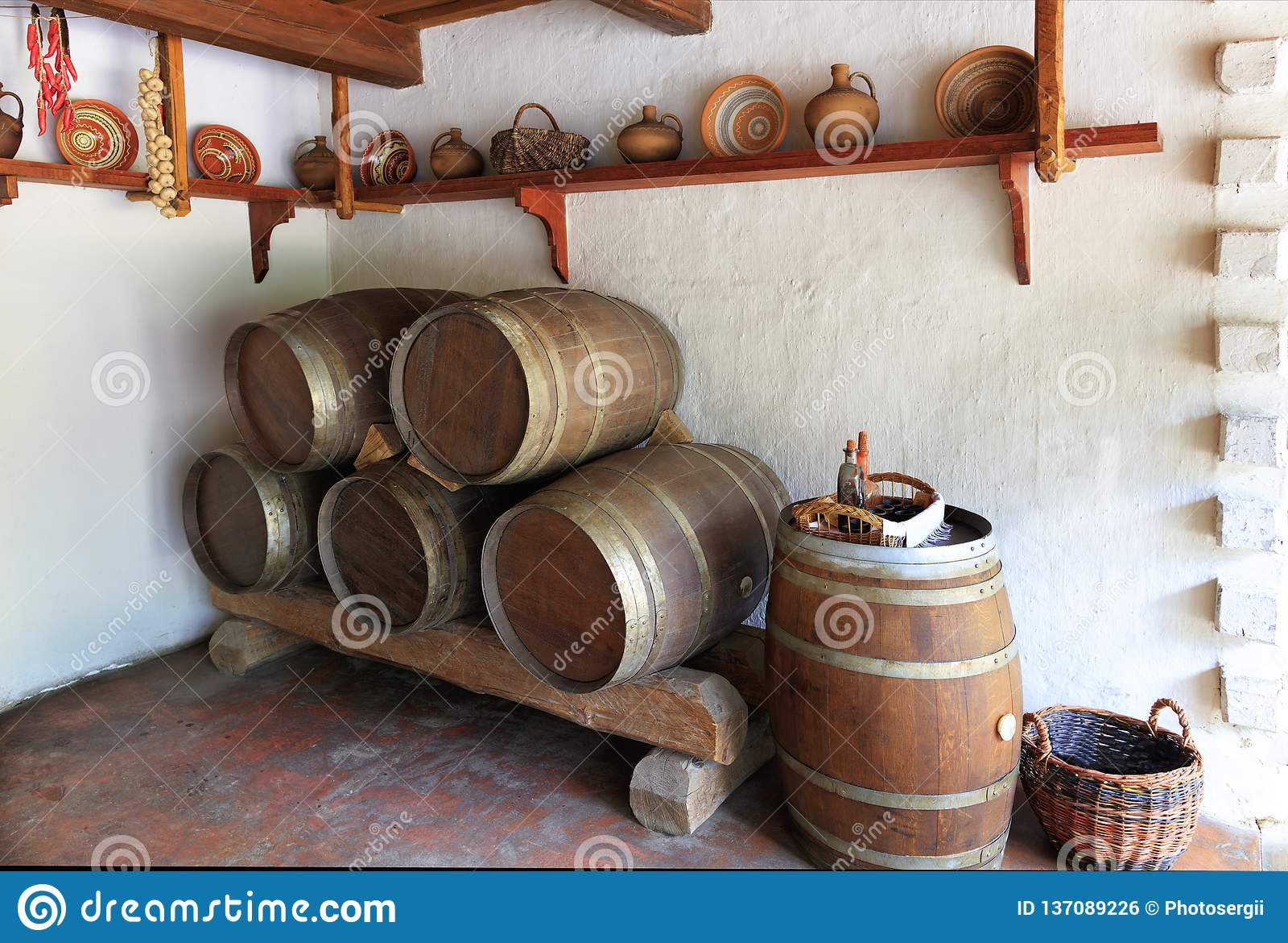Άποψη του παλαιού δωματίου κρασιού του ουκρανικού αγροτικού σπιτιού, των εργαλείων κουζινών και των ξύλινων δρύινων βαρελιών